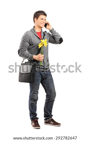 Full length portrait of a young man holding a few yellow tulips and talking on his cell phone isolated on white background - stock photo