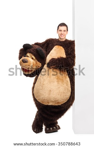 Full length portrait of a young man in a bear costume leaning against a wall and looking at the camera isolated on white background - stock photo