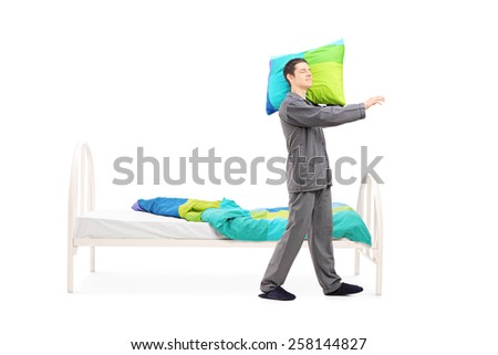 Full length portrait of a young man in pajamas sleepwalking by his bed isolated on white background - stock photo