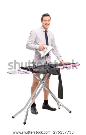 Full length portrait of a young man ironing his pants and looking at the camera isolated on white background - stock photo