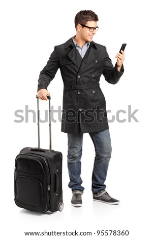 Full length portrait of a young man prepared for a yourney typing a sms isolated on white background - stock photo