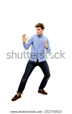 Full length portrait of a young man ready to fight - stock photo