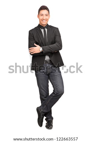 Full length portrait of a young man smiling and leaning on a virtual wall isolated on white background - stock photo