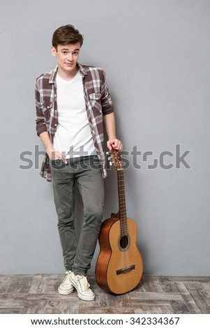Full length portrait of a young man standing with guitar on gray background - stock photo