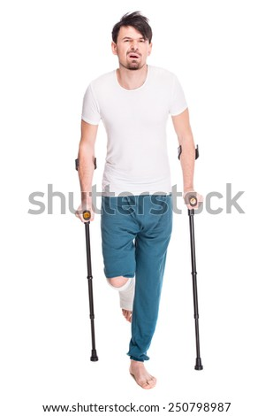 Full length portrait of a young man with broken leg is using crutch isolated on white background. - stock photo