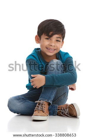 Full length portrait of a young mixed race boy sitting on the floor.  Isolated on white. - stock photo