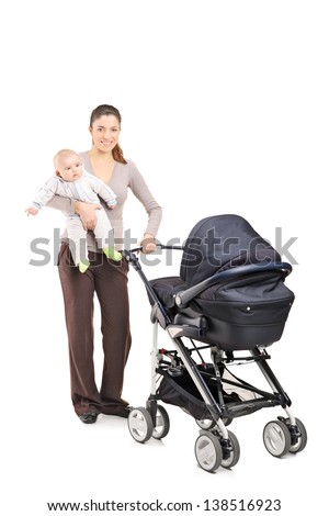 Full length portrait of a young mother with a baby and a pushchair, isolated on white background - stock photo