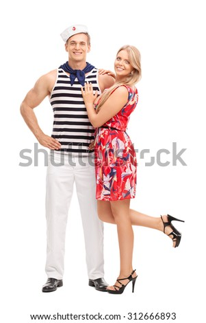Full length portrait of a young sailor hugging his girlfriend and looking at the camera isolated on white background - stock photo