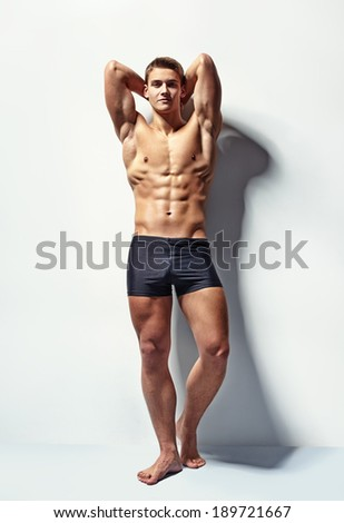 Full length portrait of a young sexy muscular male model in underwear against white wall in sensual pose his hands behind his head - stock photo