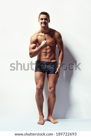 Full length portrait of a young sexy muscular man in underwear showing his muscles against white wall - stock photo