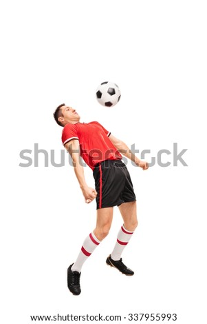 Full length portrait of a young sportsman in red jersey playing football isolated on white background - stock photo