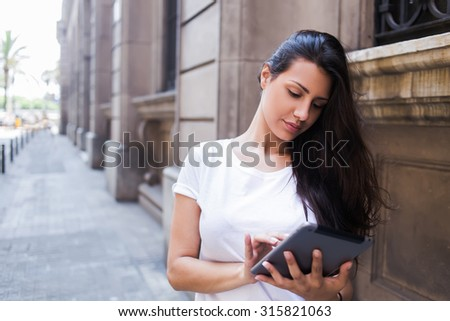 Full length portrait of a young stylish hipster girl working on her digital tablet computer while standing on the street in urban setting,gorgeous female tourist using touch pad for navigation in city - stock photo