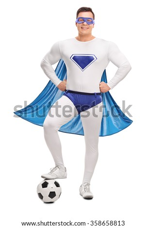 Full length portrait of a young superhero in a white and blue costume stepping over a football isolated on white background - stock photo