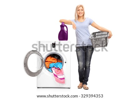 Full length portrait of a young woman holding an empty basket and leaning on a laundry detergent on top of a washing machine isolated on white background - stock photo