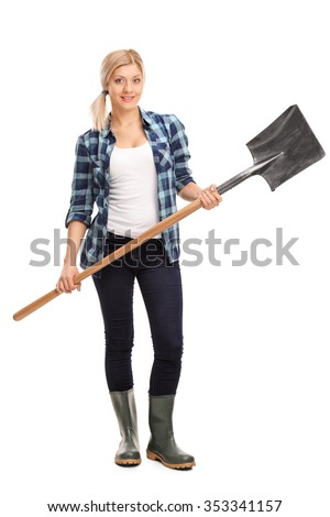 Full length portrait of a young woman in blue checkered shirt and gray rubber boots holding a shovel isolated on white background - stock photo