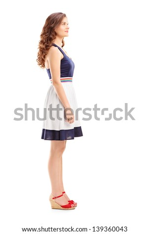 Full length portrait of a young woman in profile, isolated on white background - stock photo