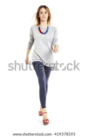 Full length portrait of a young woman walking and looking at you.  - stock photo