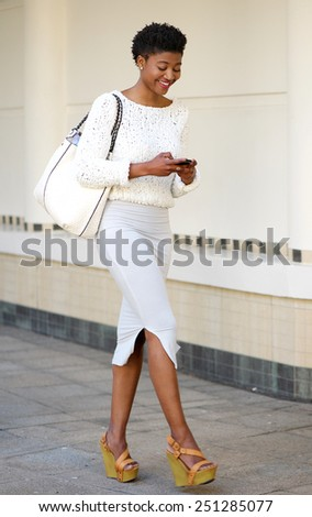 Full length portrait of a young woman walking and sending text message on mobile phone - stock photo