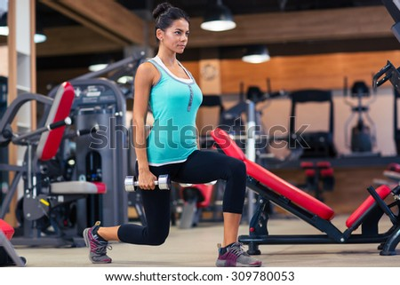 Full length portrait of a young woman workout with dumbbells in fitness gym - stock photo