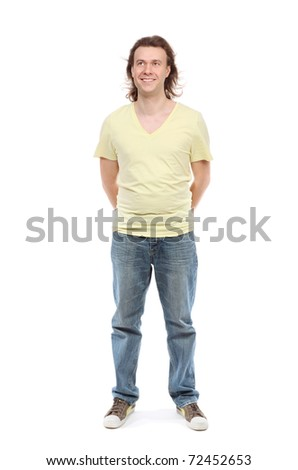 Full length portrait of adult man over 30 years with hair to shoulders in a shirt, jeans and sneakers with a little paunch, which has removed hands behind back, looking up and smiling - stock photo