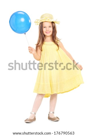Full length portrait of an adorable little girl in yellow dress holding a blue balloon isolated on white background - stock photo