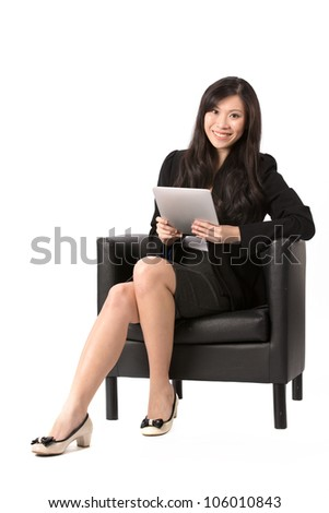 Full length portrait of an Asian Business woman sitting on a chair using Digital Tablet. Isolated on white background. - stock photo
