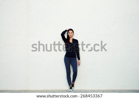 Full length portrait of an attractive and sporty young woman standing against a white background while getting ready for workout outdoors, cross process, filtered image - stock photo