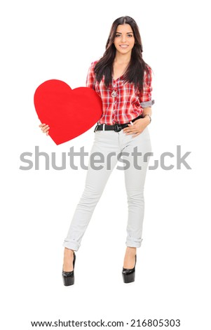 Full length portrait of an attractive female holding a red heart symbolizing love isolated on white background - stock photo