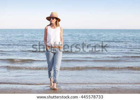 Full length portrait of an attractive mature woman walking on the beach barefoot. Beautiful female in straw hat and sunglasses wearing casual clothes. - stock photo