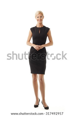 Full length portrait of an elegant businesswoman standing against white background while looking at camera and smiling. - stock photo