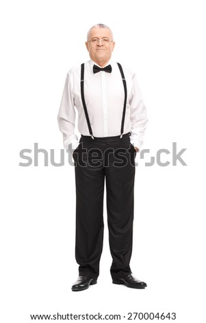 Full length portrait of an elegant cheerful senior standing with his hands in his pockets and looking at the camera  - stock photo