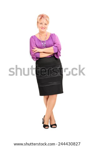 Full length portrait of an elegant mature woman leaning against a wall isolated on white background - stock photo