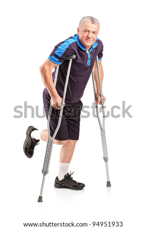 Full length portrait of an injured senior player on crutches isolated on white background - stock photo