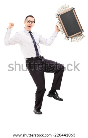 Full length portrait of an overjoyed businessman holding a briefcase full of money isolated on white background - stock photo