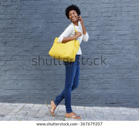 Full length portrait of an smiling young african american woman walking with a bag and talking on mobile phone - stock photo