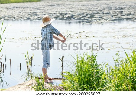 Full length portrait of angleing boy who is throwing bait of wooden green fishing rod - stock photo