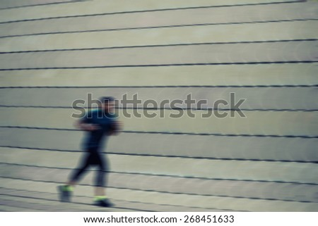 Full length portrait of athletic dark-skinned man running along beautiful grey wall outdoors, muscular build young runner working out while jogging in the park motion blur effect - stock photo