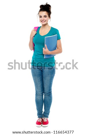 Full length portrait of attractive college girl holding notebook and backpack - stock photo