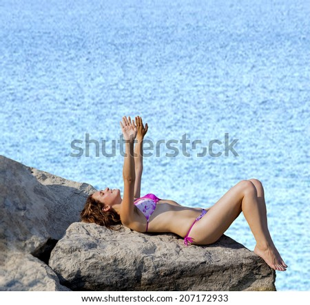 Full length portrait of Attractive redhead girl relaxing and sunbathing on a beautiful rocky sea beach lying down and pulls his hands to the sun Copy space for inscription - stock photo