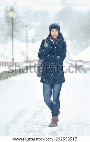 Full length portrait of attractive woman in winter park - stock photo