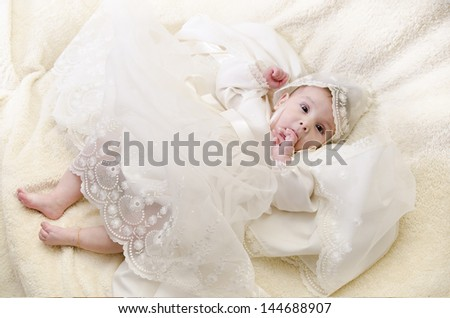Full length portrait of baby with christening clothes. - stock photo