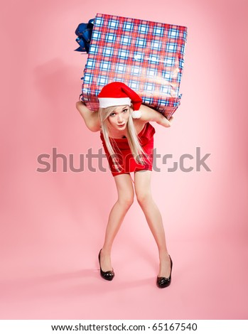 full-length portrait of beautiful blonde xmas girl carrying heavy gift box on pink - stock photo