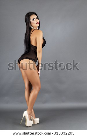 Full length portrait of beautiful brunette woman posing in sexy black lingerie and high heels over gray background - stock photo