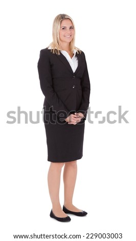 Full length portrait of beautiful businesswoman standing with hands clasped over white background - stock photo