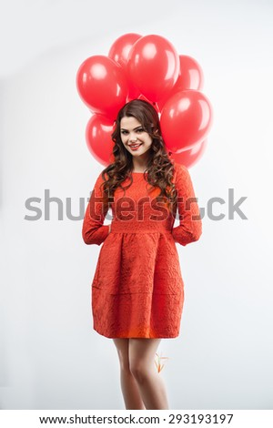 Full length portrait of beautiful girl smiling and standing in the studio. She is hiding balloons behind her back secretly. Isolated on grey background - stock photo