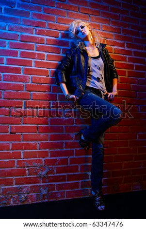 full-length portrait of beautiful glam rock style blonde girl standing near red brick wall on one leg - stock photo
