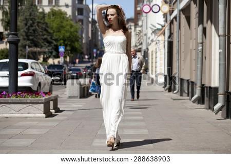 Full length portrait of beautiful model woman walking in white dress in summer street - stock photo