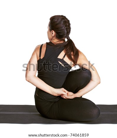 full-length portrait of beautiful woman working out yoga excercise ardha matsyendrasana (half spinal twist) on fitness mat - stock photo