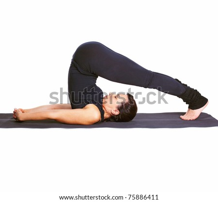 full-length portrait of beautiful woman working out yoga excercise halasana (plough pose) on fitness mat - stock photo