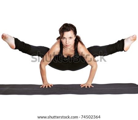 full-length portrait of beautiful woman working out yoga excercise tittibhasana - standing on hands ad doing the spilts on fitness mat - stock photo